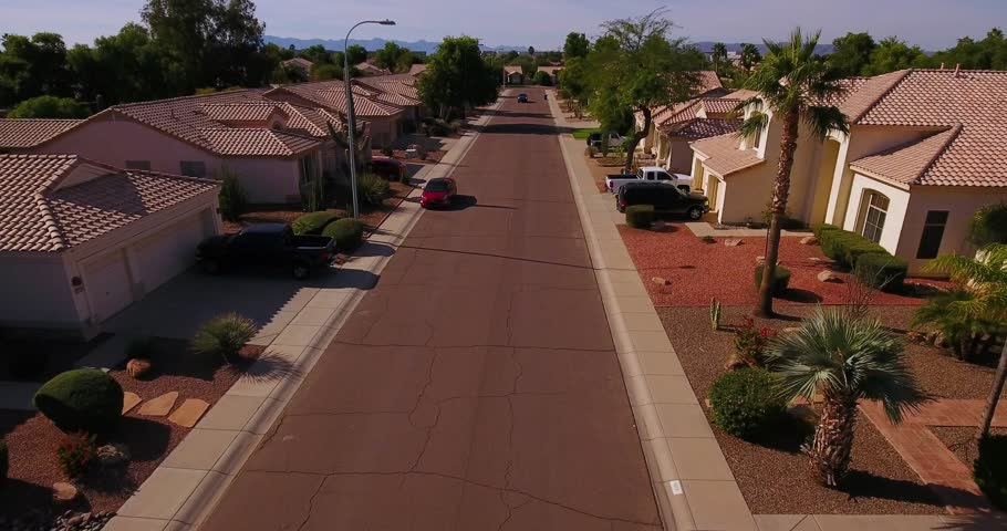 A truck drives past homes in a typical Arizona neighborhood. Phoenix suburbs.