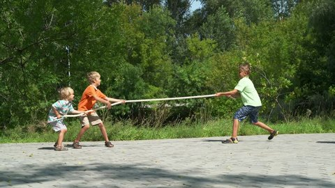 Three happy boys playing tug-of-war in park. Kids pull the rope in sunny day. Summer fun.