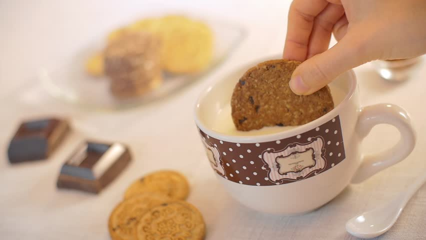A woman hand dunks a cookie in the milk mug during the breakfast in a warm morning. Camera slider slow motion shot