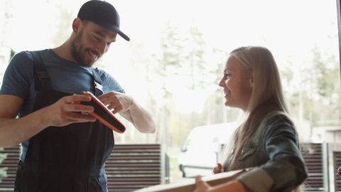 Beautiful Homeowner Opens the Door to Smiling Delivery Man and Receives Parcel After Signing on Electronic Signature Device. Shot on RED Cinema Camera in 4K (UHD).