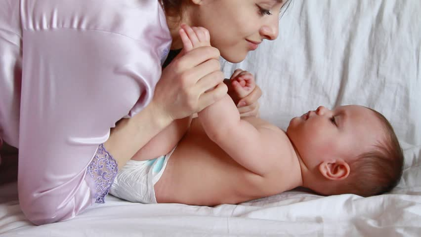 Beautiful mother kissing small baby girl