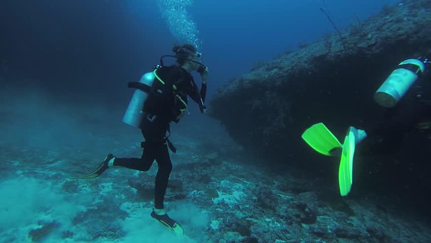 Divers swim underwater with aqualungs. Blue clean ocean. Deepness. Sealife. Fish. Active hobby | Shutterstock HD Video #21557227