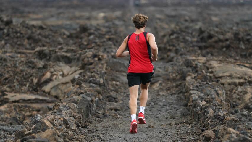 57ea5387f085 Man running - trail runner training on amazing lava waking trail on Hawaii  training for marathon or triathlon ironman. Male athlete working out on Big  ...