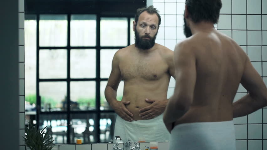 Unhappy, sad man checking his belly in front of mirror in bathroom