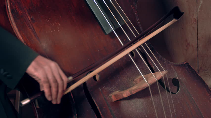 Bassist playing / Contrabass Player / Orchestra Musician. Bassist playing old dusty contrabass at a classical music concert. Bass and bow close-up. (av24803c)