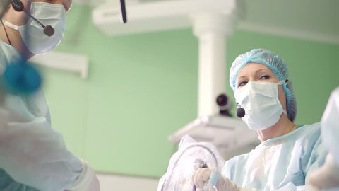 Doctor performs endoscopic surgery removing a brain tumor.