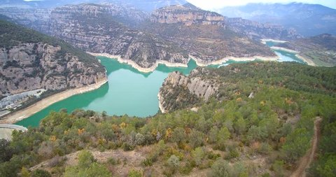 Aerial: 123 m dam of Llosa del Cavall reservoir with turquoise waters, and C462 road with car. In Pyrenees mountains, Europe