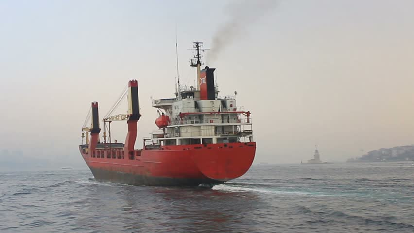 Back view of the cargo container ship. Red cargo ship