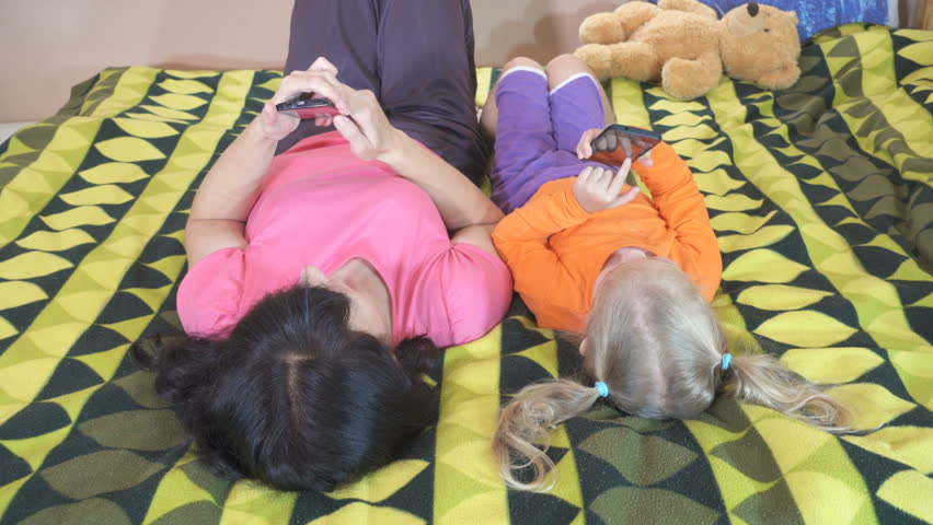 Little daughter and mother using smartphones lying on the bed. | Shutterstock HD Video #21676759