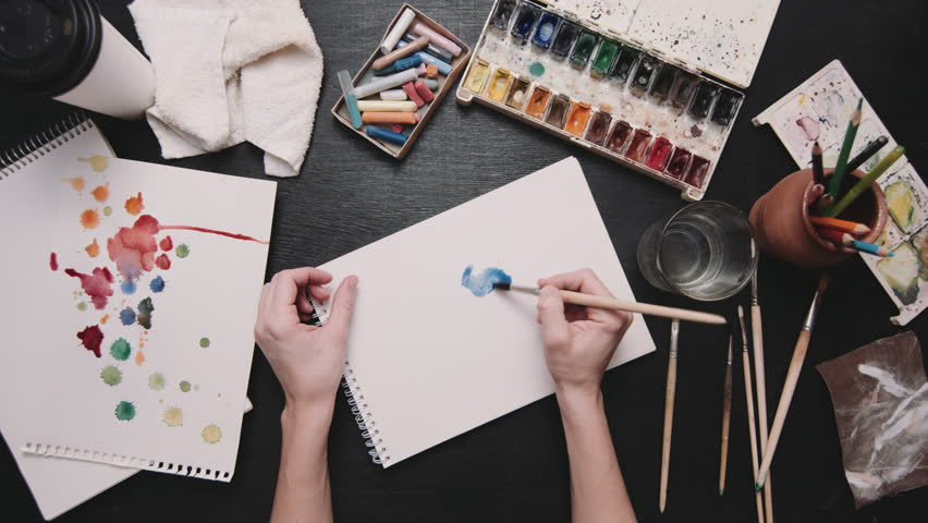 From above shot of crop hands drawing on paper with water color paints on workplace of artist. | Shutterstock HD Video #21706909