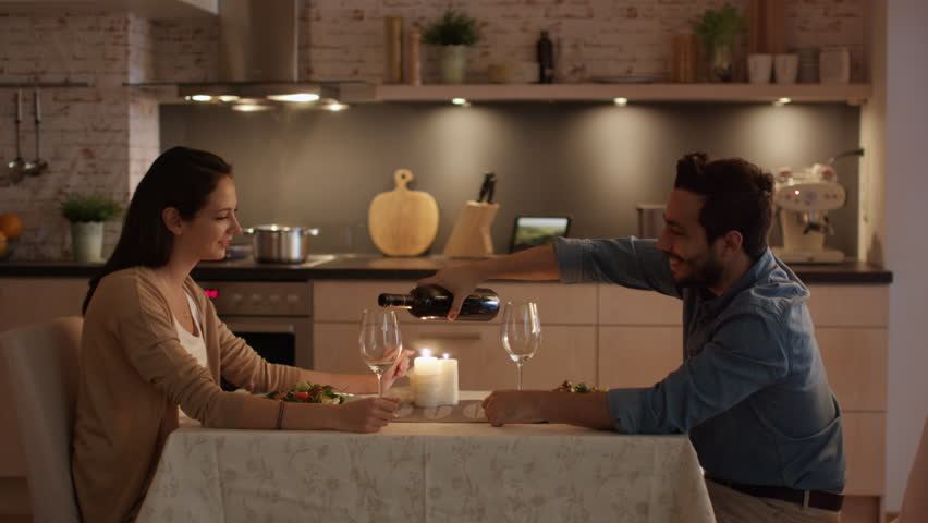 Young Couple Having Candlelight Dinner. Talking. Man Pours Wine in Glasses. Shot on RED Cinema Camera in 4K (UHD).