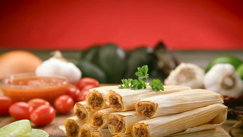 Tamales with husks stacked on a wood chopping board, surrounded by limes, cherry tomatoes, garlic cloves, salsa bowel, whole avocados and a yellow onion.