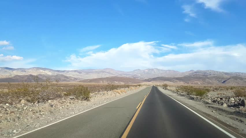 Driving view from a cars window with praerie and mountains, in Death valley, California, in United states of America