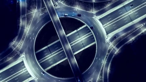 Elevated Road Junction And Interchange Overpass  At Night Traffic Timelapse Transportation Light Dark Illuminated Modern Urban Office Building