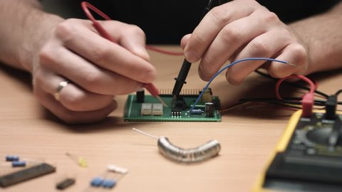 Close up of repairman's hands check electronic circuit on circuit board with multimeter