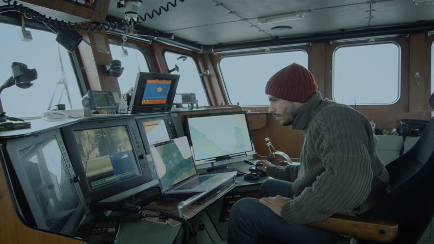 Captain of Commercial Fishing Ship Surrounded by Monitors and Screens Working with Sea Maps in his Cabin. Shot on RED Cinema Camera in 4K (UHD).