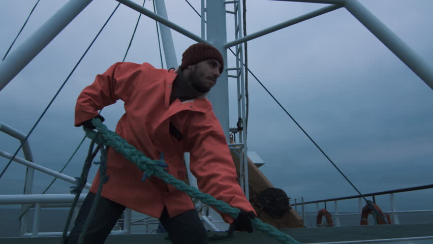 Serious Seaman Pulls the Thick Rope during Traveling on the Ship. Shot on RED Cinema Camera in 4K (UHD).