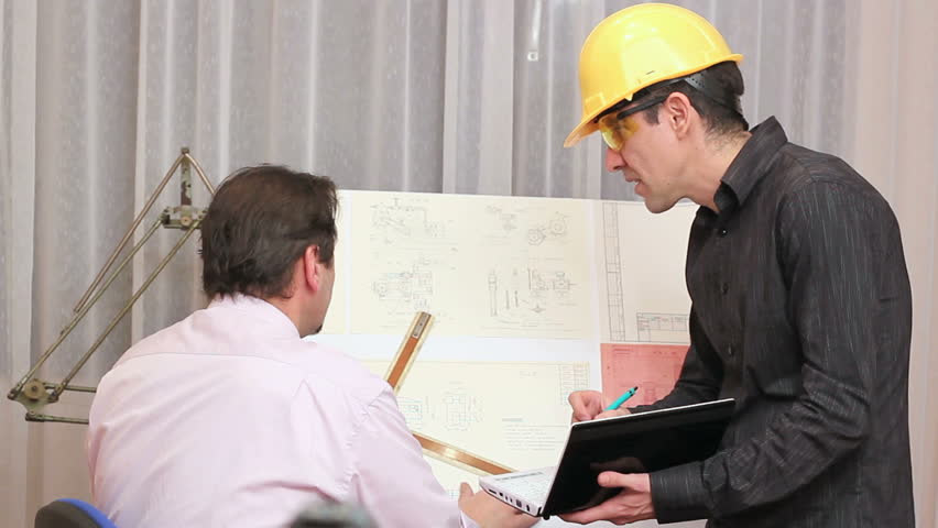 Two male engineers discussing on a blueprint. Successful Business Team in an Office.  Business people working late at the office. Two Architects Discussing a Project.