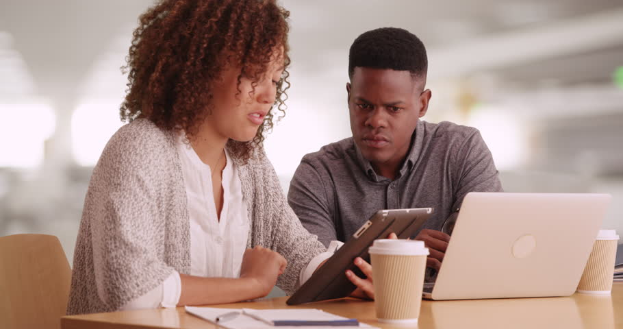 Millennial coworkers comparing notes using tablets and laptops. Young corporate professionals using PC and pad. Black man and woman in their 20s working at contemporary office using technology. 4k. | Shutterstock HD Video #21850729