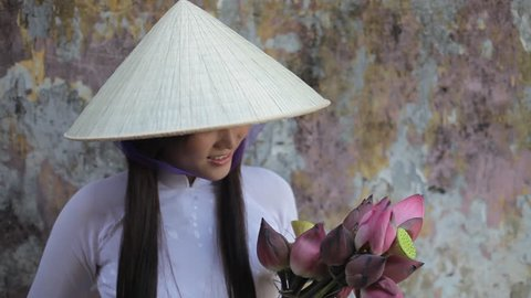 MH LD Young Woman Wearing Ao Dai and Straw Hat Holding Flowers / Hoi An, Vietnam