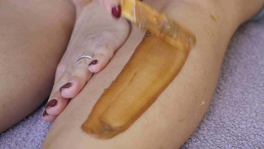 Close-up of woman leg depilation professional work 4K 2160p 30fps UltraHD footage - Hard warm wax on female body parts done in the studio 3840X2160 UHD video