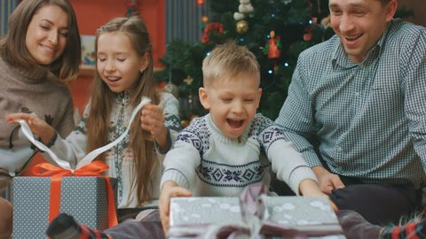 Happy children open Christmas gifts with parents, New Year