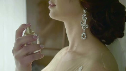 Closeup of a bride using perfume on her wedding day