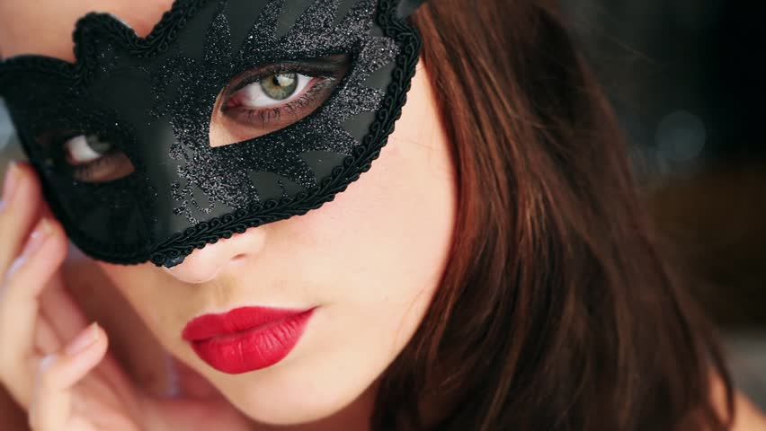 Sexy woman wearing masquerade mask stroking her neck flirting at party