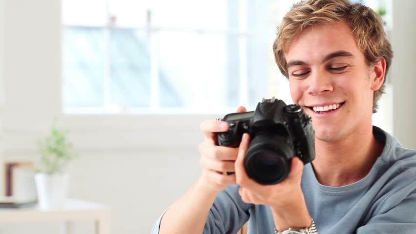 Attractive young man taking photographs with dslr digital camera at home #2192332