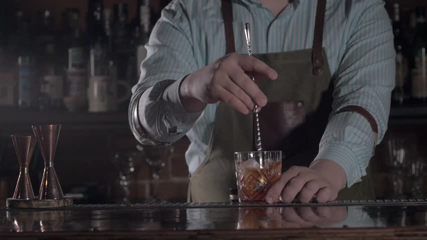 Bartender is stirring cocktails in mixing glasses, modern bar