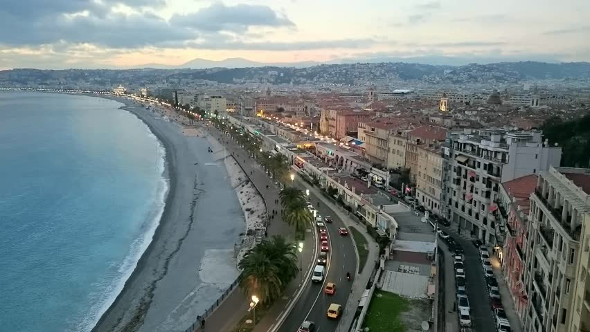 Timelapse view over city of Nice France late afternoon to early night with moving clouds, blue sky and traffic lights