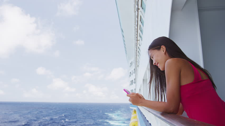 Smartphone woman texting using social media app on cruise ship travel vacation looking at display screen for sms reading on ocean background on balcony. Girl using smart phone on holiday.