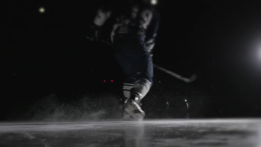 Ice hockey player shoots the puck, power slap shot in canadian style by professional athlete.