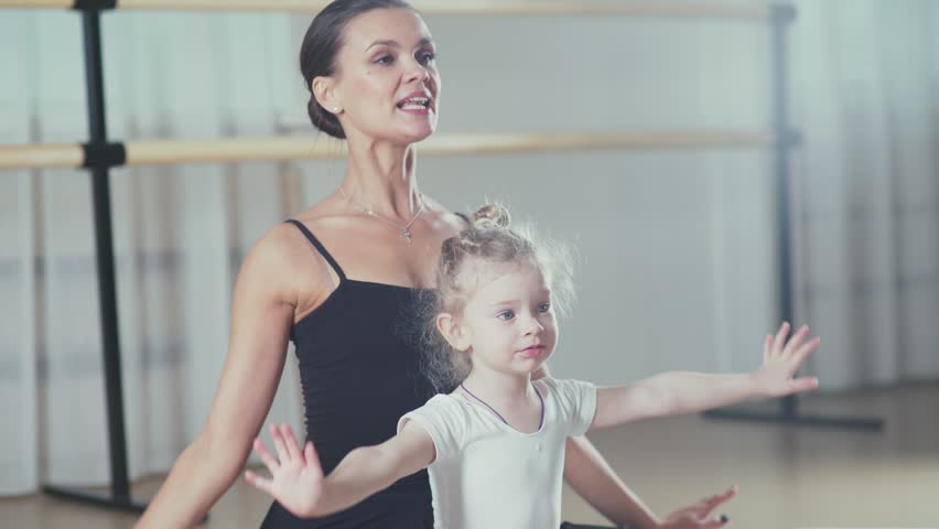 A woman and a girl in a ballet school. Beautiful and statuesque female ballerina doing stretches with a little girl. Adult ballerina practicing with the little girl and trains Russian classical ballet