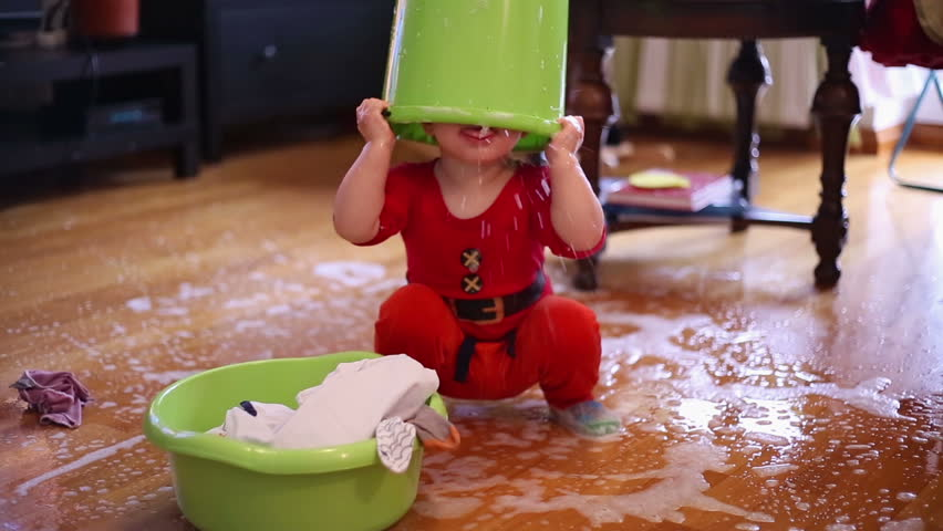 Cute baby toddler playing with spilled water on the floor at home