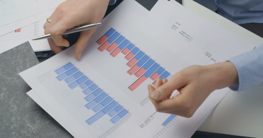 Top view of a female accountant reading documents with charts and financial information. | Shutterstock HD Video #21989839