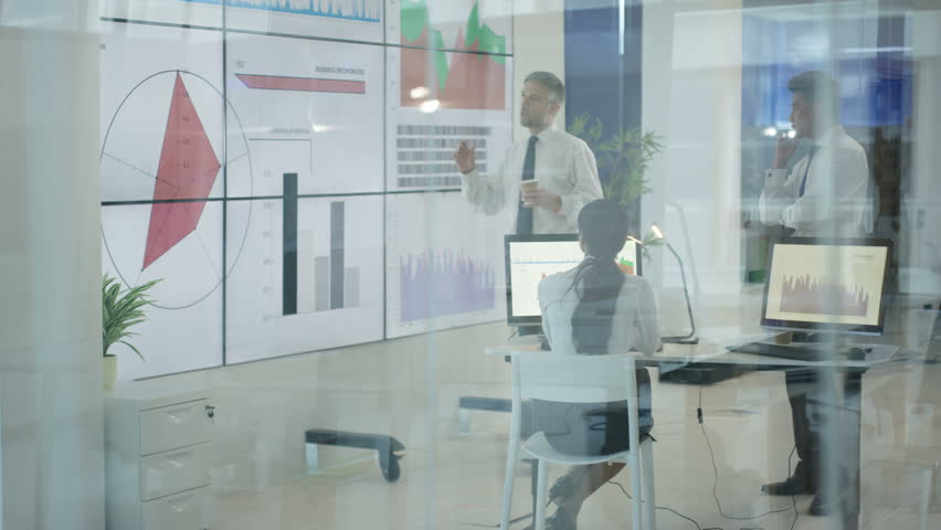 4K Business team in modern office, looking at video wall with graphs and data (UK-Oct 2016) #21992419