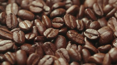 beautiful background of roasted steaming coffee beans which rotate in slow motion
