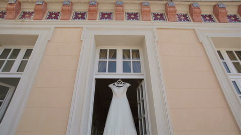 Wedding dress hangs in doorway at balcony tracking pan vertical light. Decorated lace white bridal gown on hanger waits for bride in medieval ancient terrace decor elements. Morning bride preparations