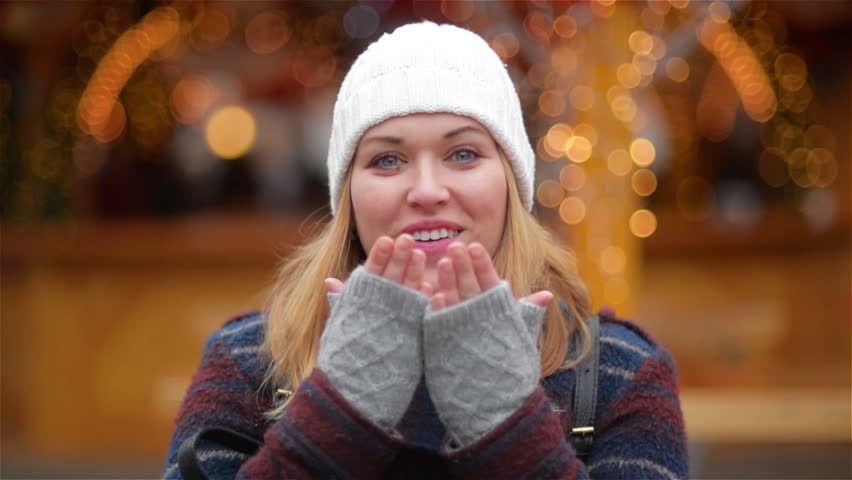 Happy Carefree Woman With Blonde Hair Sends An Air Kiss Over Christmas Lights Background. Beautiful Girl Wearing A White Hat And Grey Mitts Is Smiling On The New Year Fair.
