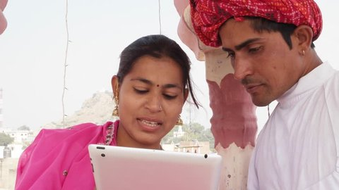 Rajasthani couple working learning teaching sharing on a tablet wearing pink sari and red turban in India