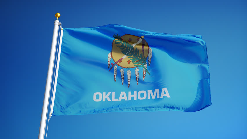 Oklahoma (U.S. state) flag waving in slow motion against blue sky, seamlessly looped, close up, isolated on alpha channel with black and white matte, perfect for film, news, composition