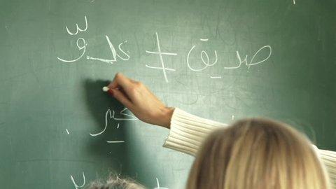 Tilt-down from blackboard to expat primary schoolgirls listening while the teacher is at the blackboard teaching an Arabic language grammar class, in a Dubai primary school. (Dubai, UAE-2013)