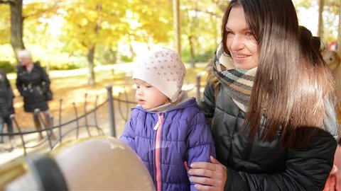 Smiling Mother and Kid Riding on Carousel in the Autumn Park During a Day. Beautiful Woman and Cute Girl Having Fun Together Outdoors Sitting on a White Horse in a Roundabout