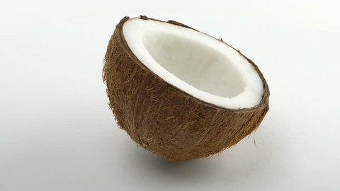 One half of a ripe tropical coconut rotating on a white background. Tropical fruits. Loopable.