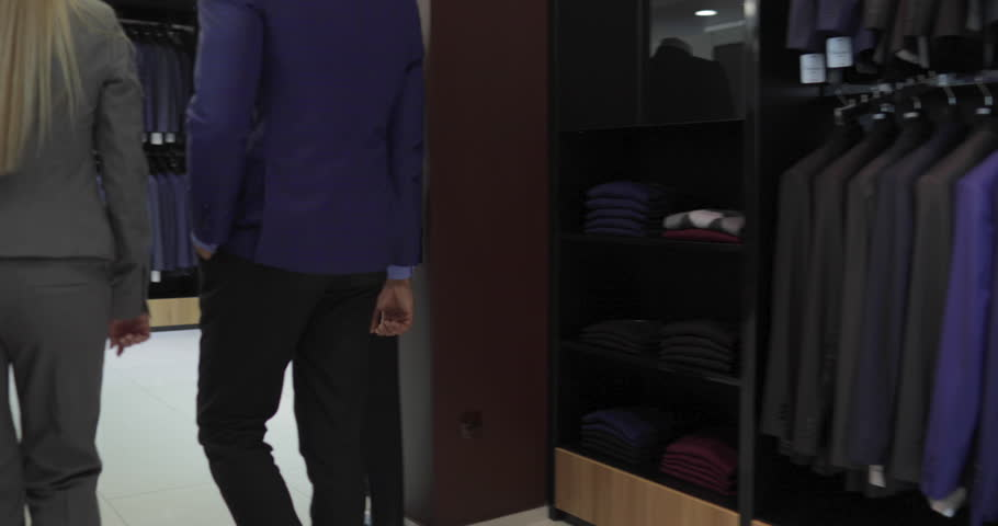 Business Man Enter Fashion Shop, Customer Choosing Suit Clothes In Retail Store, Shopping Seller Woman Show Formal Wear Slow Motion 60 Fps | Shutterstock HD Video #22130149