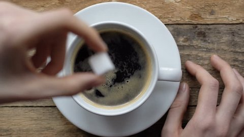 block of sugar is falling from top in coffee cup with black espresso in slow motion