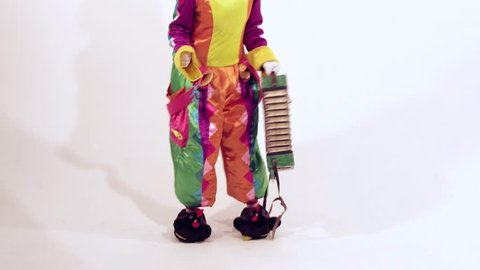 Circus clown dressed in funny colorful costume is enjoying her dance