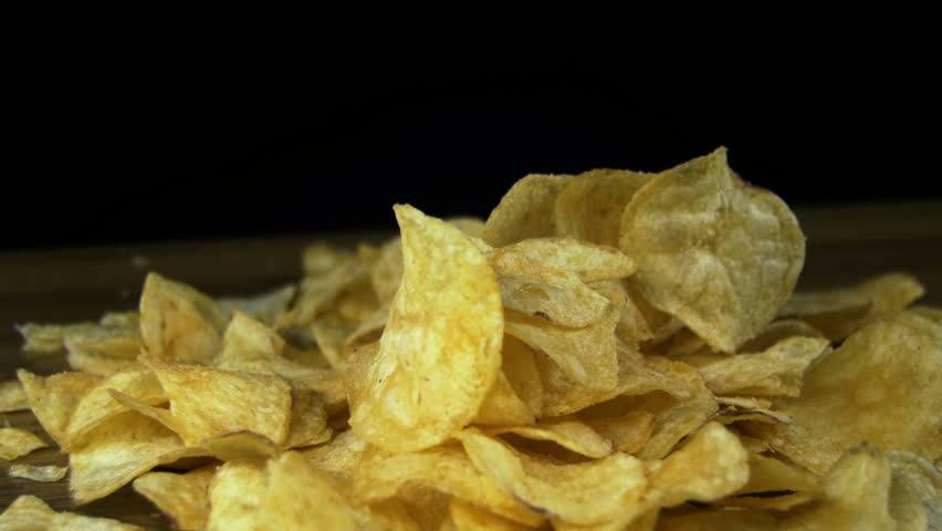 Potato Chips Rotating On Black Background. Potato chips are rotated on a black background. Close-up of yellow delicious chips randomly lying on a table. Excellent Footage for themes: Harmful food | Shutterstock HD Video #22146508