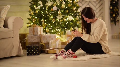 Beautiful Emotional Brunette Texting on her Gadget and Smiling Next to Large Christmas Tree and a Boxes with Gifts. Young Woman with Long Dark Hair Sitting on the Floor Using Phone.